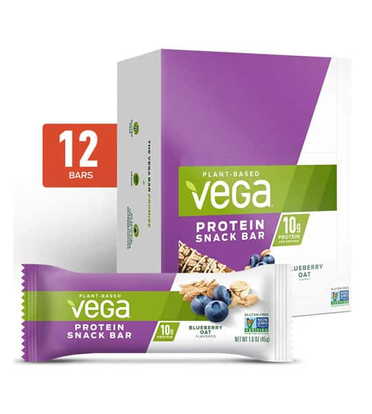 Purple and white box and a pouch of Vega plant based protein snack bar with blueberry oat flavour